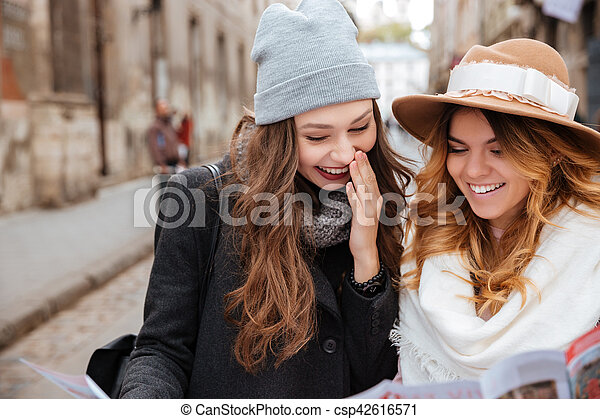 Models outdoor. in coats. in hats. smiling. on the street