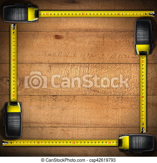 Frame made with four tape measures on a wooden background with copy space