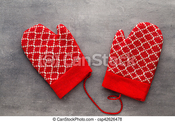 Christmas gloves on the gift card wooden background.