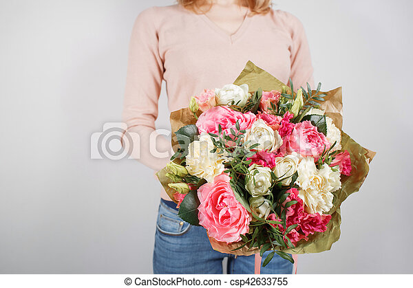 Florist at work. Make rich bouquet diferent color and flowers. Bunch in their hands.