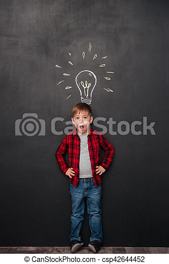 Picture of a little surprised boy having an idea over chalkboard background with drawings. Look aside.