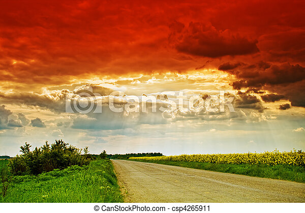 Rural road, sun rays and dramatic cloudy sky - csp4265911