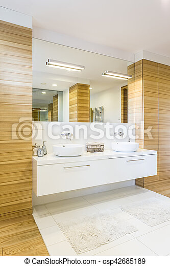 Large spacious bathroom finished in wood with large mirror and two white sinks