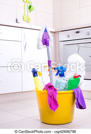 Cleaning supplies and equipment in bucket on kitchen floor with oven and cabinets in background