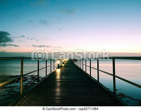 Long wooden pier on the Baltic coast during autumn morning. Cold weather, cold water. Empty mole