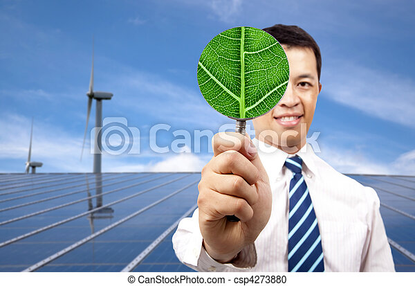 green energy business concept.young businessman holding Magnifier and standing in front of solar panel and wind turbine - csp4273880