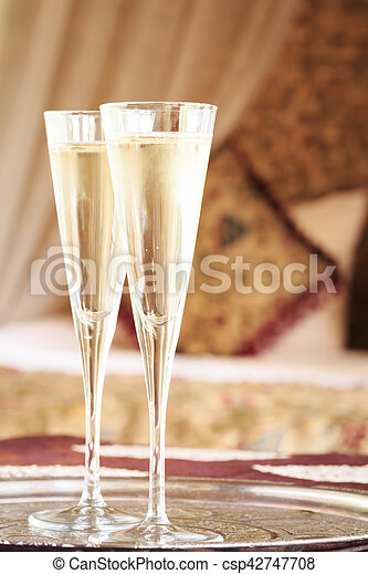 Two champagne glasses with oriental canopy bed at the background. Silver tray. Romantic concept. Valentines background. Arabian nights ambiance. Vertical, close up