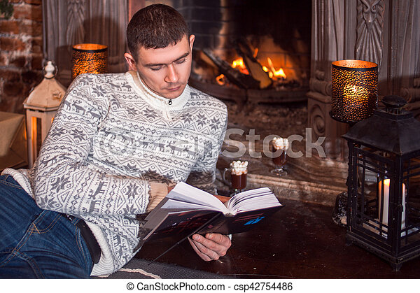 Man and woman in knitted sweater sitting on the floor by the fireplace