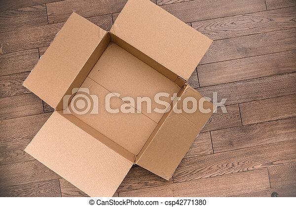 a open empty carton box on wood floor
