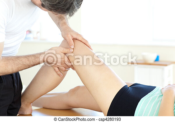 Handsome young physical therapist giving a leg massage - csp4280193
