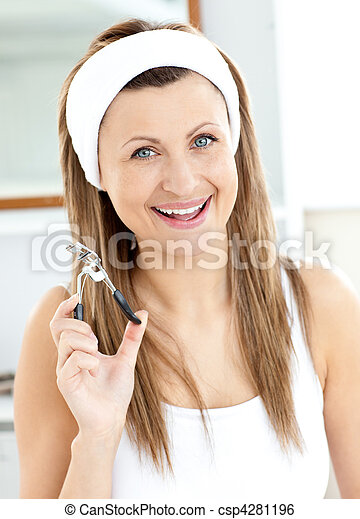 Cheerful woman holding an eyelash curler looking at the camera in the bathroom at home - csp4281196