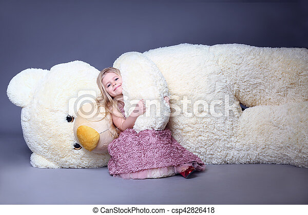 Girl hugging big teddy\'s bear arm, stuffed animals, plush animals, big plush toys, kids and gifts, lilac dress, blonde girl, baby in studio,