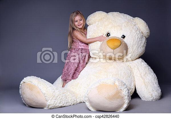 Little girl hugging big teddy bear, stuffed animals, plush animals, big plush toys, kids and gifts, lilac dress, blonde girl, baby in studio,