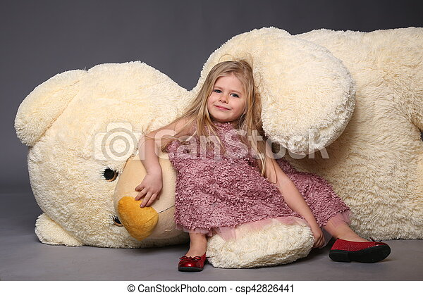 Little girl in dress laying on the big teddy bear, stuffed animals, plush animals, big plush toys, kids and gifts, lilac dress, blonde girl, baby in studio,