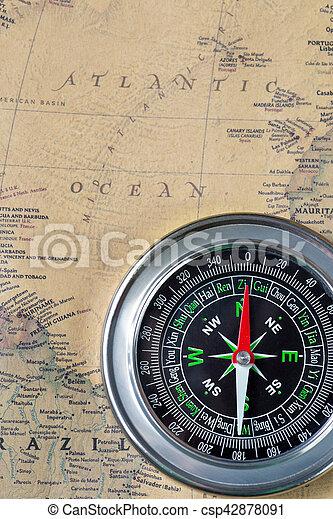 Black compass on old vintage map, atlantic ocean, macro background