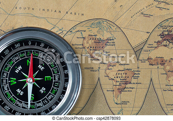 Black compass on old vintage map, north and south America, macro background