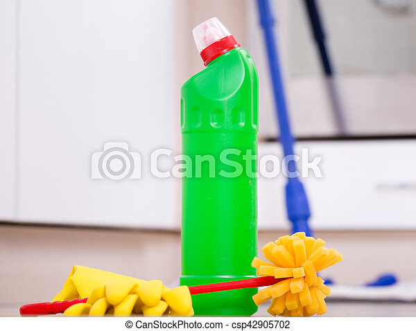Close up of bottle with disinfectant, protective gloves and brush on kitchen floor and oven in background. House cleaning concep