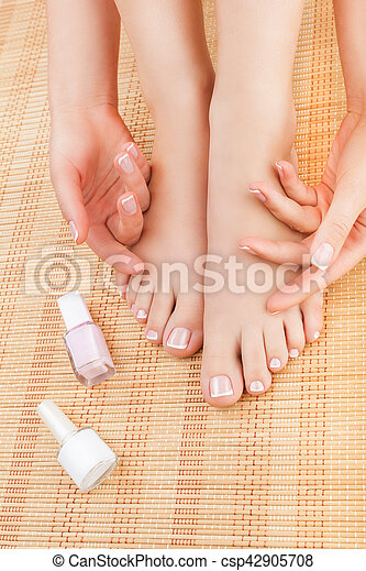 Close-up of woman\'s hands and feet after pedicure and manicure on a bamboo mat