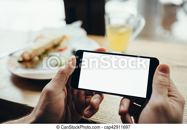 Young man\'s hands holding mobile phone. He is sitting in restaurant or cafe and watching on the screen. Place for your advertisment or logo. Back view. Close-up. Vertical position of the phone