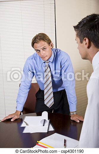 Skeptical office worker looking at colleague in boardroom - csp4301190