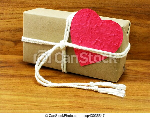 gift box wrapped in recycled paper with white rope and pink heart paper tag