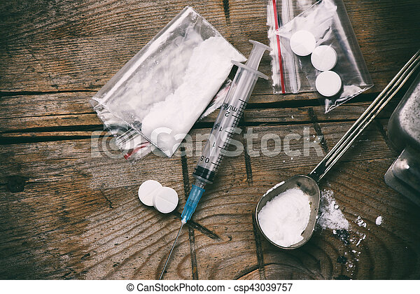 Drug, syringe and heroin on grunge wooden background