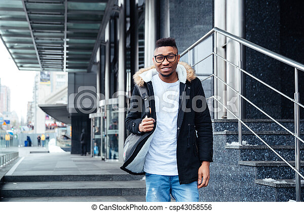 Image of a cheerful african young man wearing backpack walking on the street. Looking at camera.