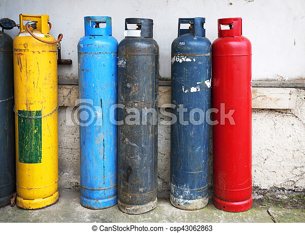 Gas cylinder. Industrial propane butane bombs. Row dirty gas cylinders. Yellow chemical bomb. Corroded welder container. Old heating bombs with valve. Pressurized container. Dangerous equipment.