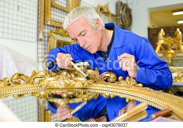 Man restoring gilt mirror - csp43076037