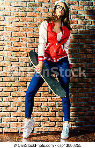 Full length portrait of an attractive girl with bright red lips wearing modern sports clothes. College style. Hipster girl by a brick wall. Youth fashion.