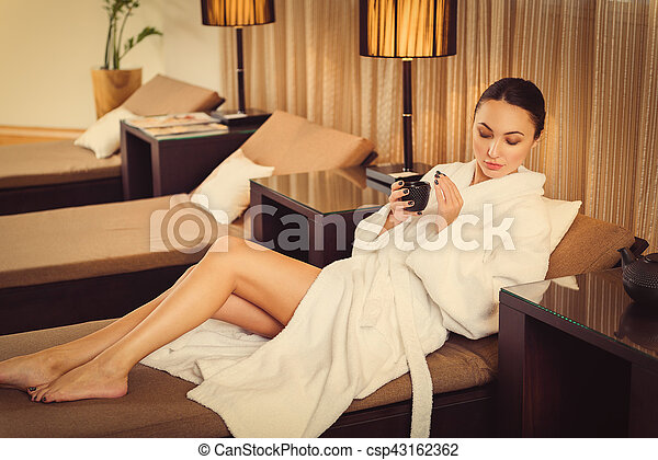 Serene girl is relaxing after spa procedure in rest room. She is lying on bed and drinking tea. Her eyes are closed with pleasure