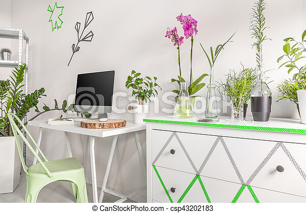 Shot of a white chest of drawers and a minimalist computer desk in a bright room interior