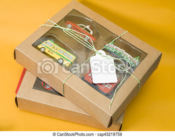 Gift boxes with toys and a blank label for text and design, studio shot on orange