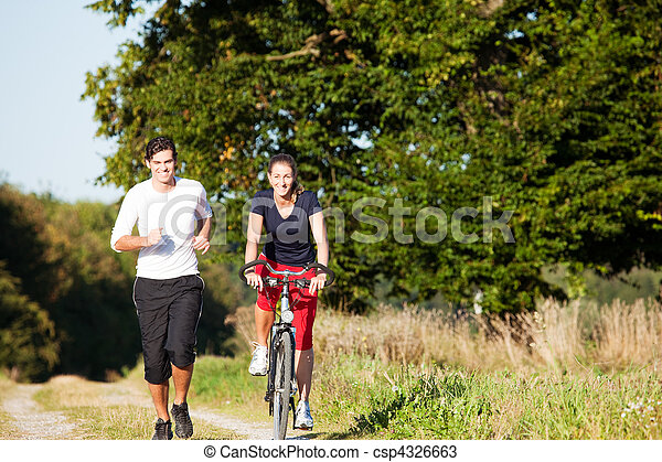 Young sport couple jogging and cycling - csp4326663