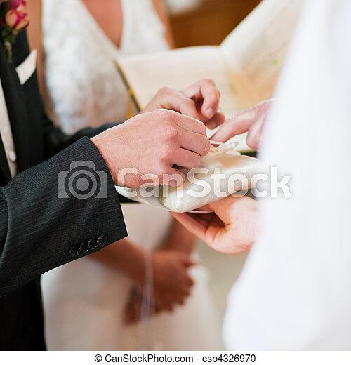 Stock Photo Groom taking rings in wedding ceremony