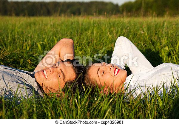 Couple sleeping on meadow in the sunshine - csp4326981
