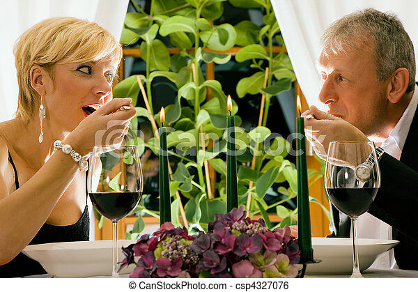 Couple having dinner in a restaurant, candles on the table, they are eating pasta