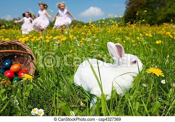 Children on Easter egg hunt with bunny - csp4327369
