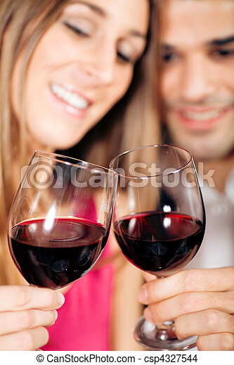 Couple drinking red wine clinking glasses - csp4327544