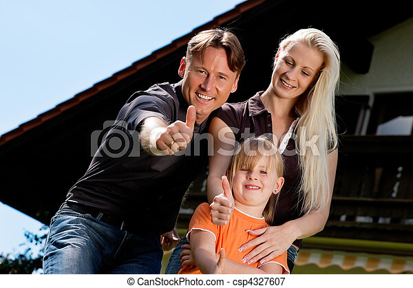 Family standing in front of their home - csp4327607
