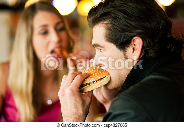 Couple in Restaurant eating fast food - csp4327665