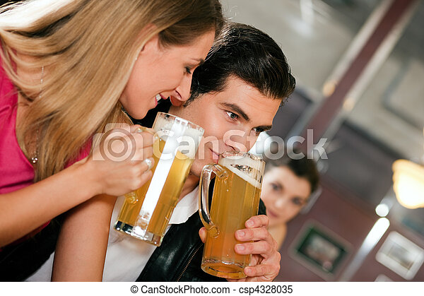 Couple in bar drinking beer flirting - csp4328035
