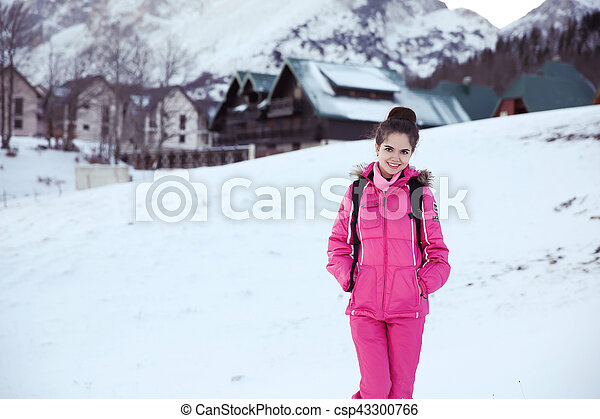 Happy free brunette woman enjoying winter vacations in front of mountains covered peak with snow. Joyful female having fun outdoors.