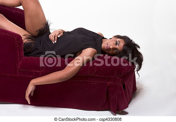 Glamorous model Afro American woman on red couch - csp4330808