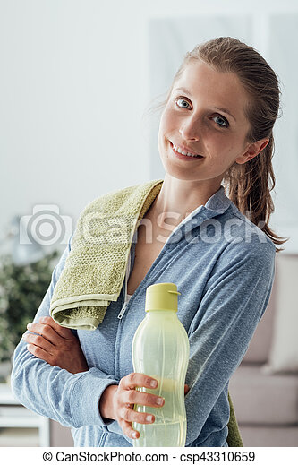 Smiling confident woman posing with a towel and a water bottle after working out, fitness and healthy lifestyle concept