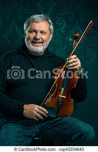 Senior musician playing a violin with a wand on black studio background