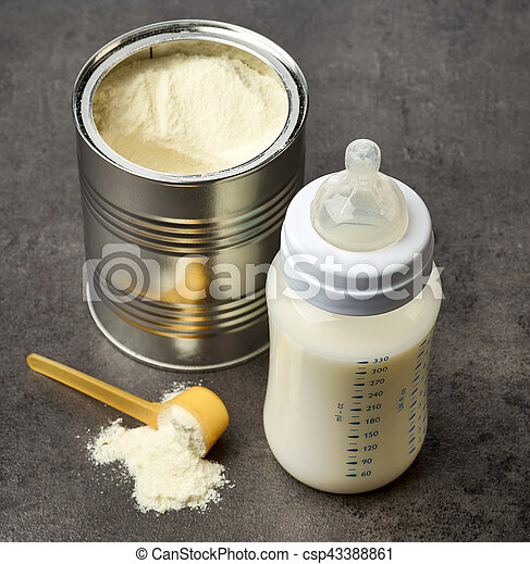 Baby bottle and milk powder on dark grey table, selective focus