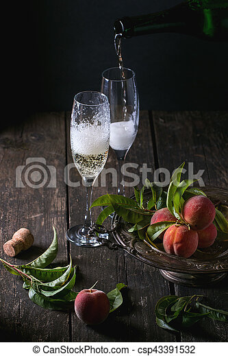 Peaches on branch with leaves in vintage plate and two glass of champagne with cork over old wooden table. Champagne pouring from bottle. Dark rustic style.