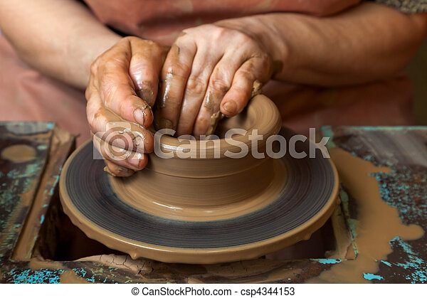 Potter creates a pitcher on a pottery wheel - csp4344153