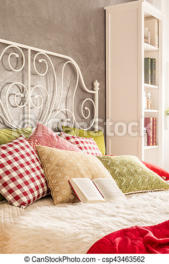 Bed with decorative metal headboard and colorful pillows